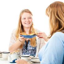 Beautiful blond teen girl having a tea party with her mother.  I