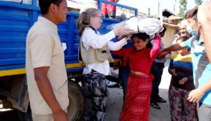 Line Højland fra Mission Øst overrækker en presenning til en kvinde, der nu kan beskytte sin familie mod regnen. Fotos: Susanne Madsen, Mission Øst