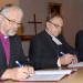 Fra venstre ses biskopperne Thor Henrik With, Norge, Risto Soramies, Finland, og Roland Gustafsson, Sverige, underskrive aftalen mellem de 'oprørske' lutherske stifter.