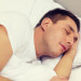 hotel, travel and happiness concept - handsome man sleeping in b