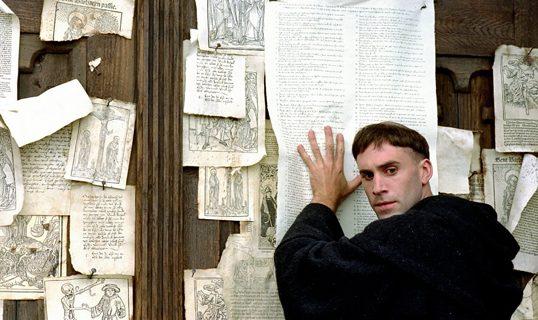 "I filmen ""Luther"" fra 2003 spiller Joseph Fiennes rollen som munken Martin Luther, der i sin kamp mod afladshandlen slog 95 teser op på døren til Wittenberg Slotskirke den 31. oktober 1517."